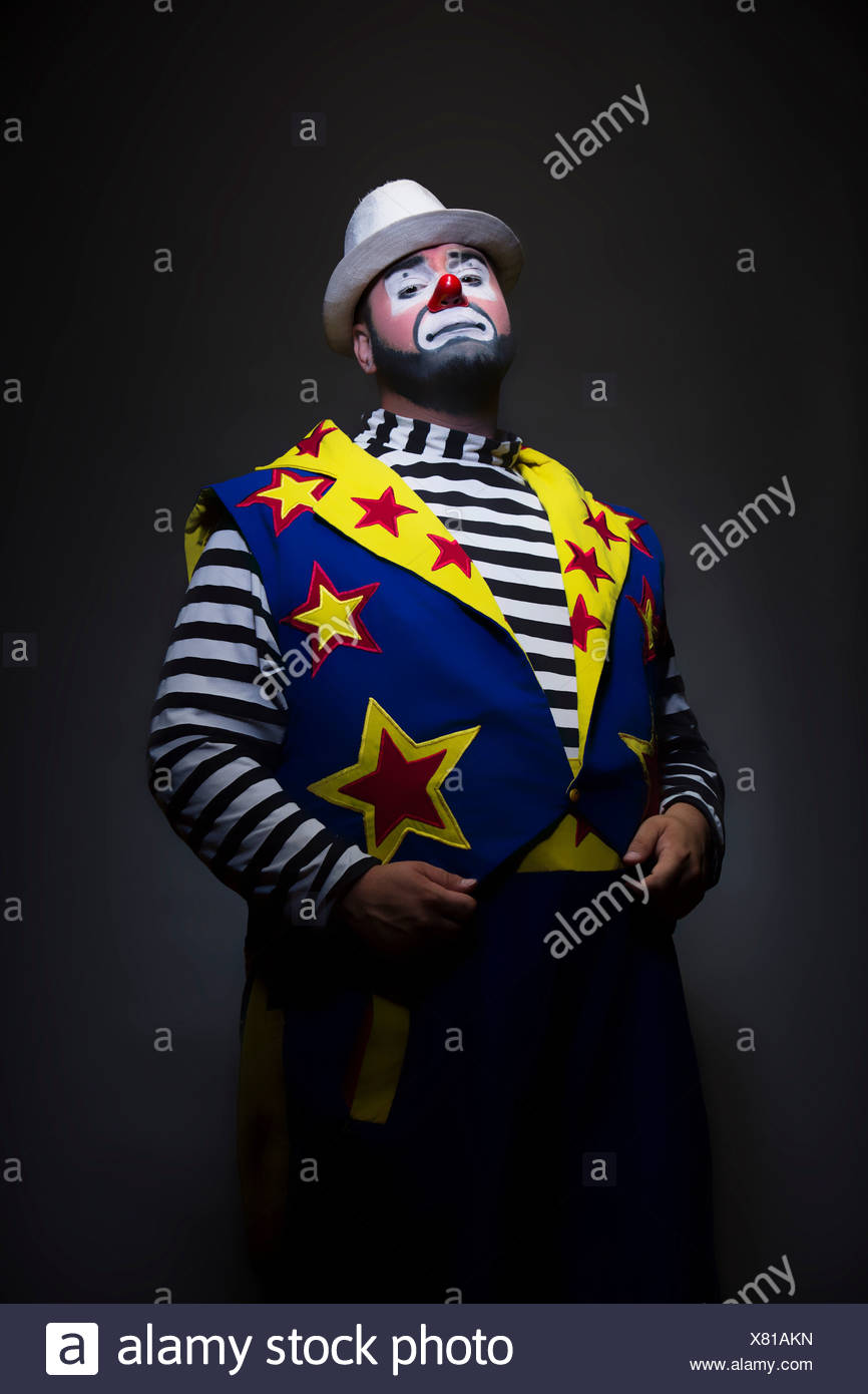 Studio portrait of clown with hands in pockets - Stock Image