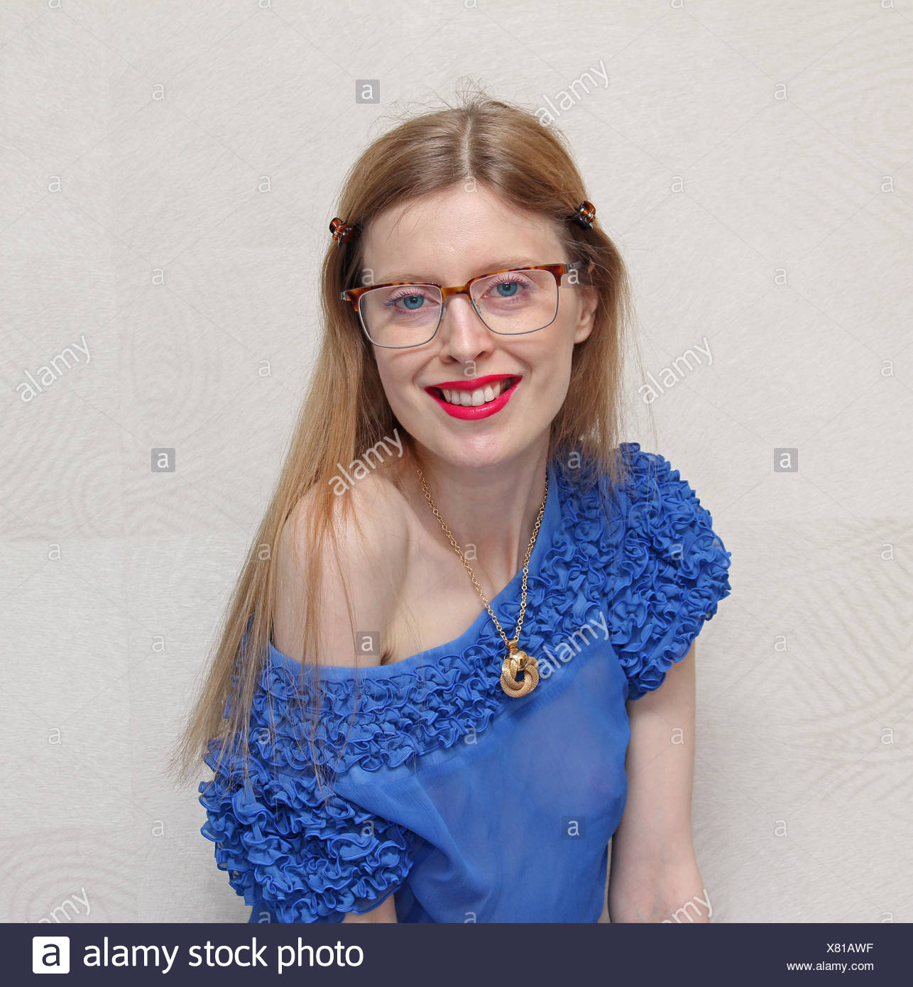 Young student with geek looking eyeglases but chic clothes and makeup - Stock Image
