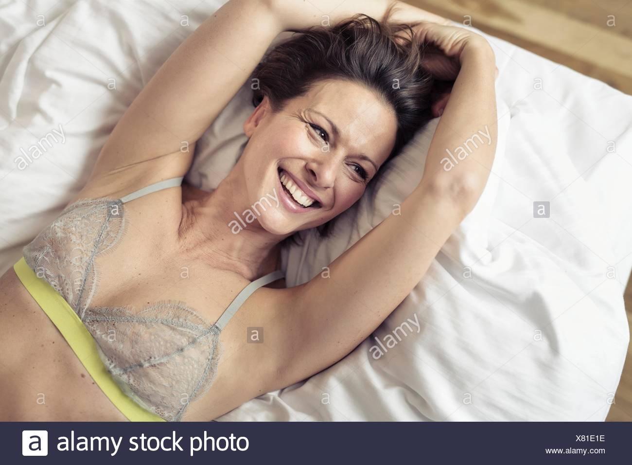 Overhead view of mature woman wearing bra lying on bed - Stock Image
