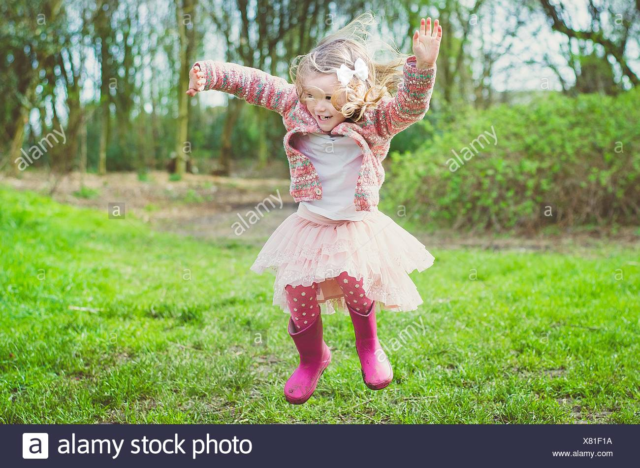 Girl jumping in the air in park - Stock Image
