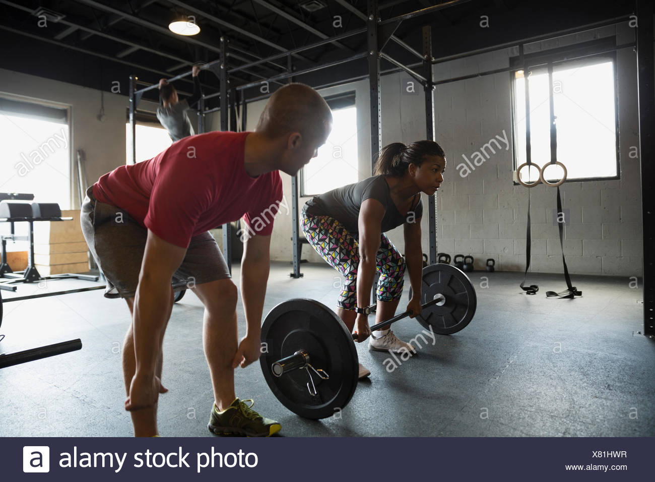 Personal trainer guiding woman weight lifting barbell - Stock Image