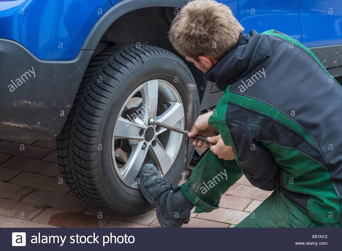 Junger Mann beim tauschen der Autoreifen. Von Sommerreifen auf Winterreifen an seinem Auto. - Stock Image