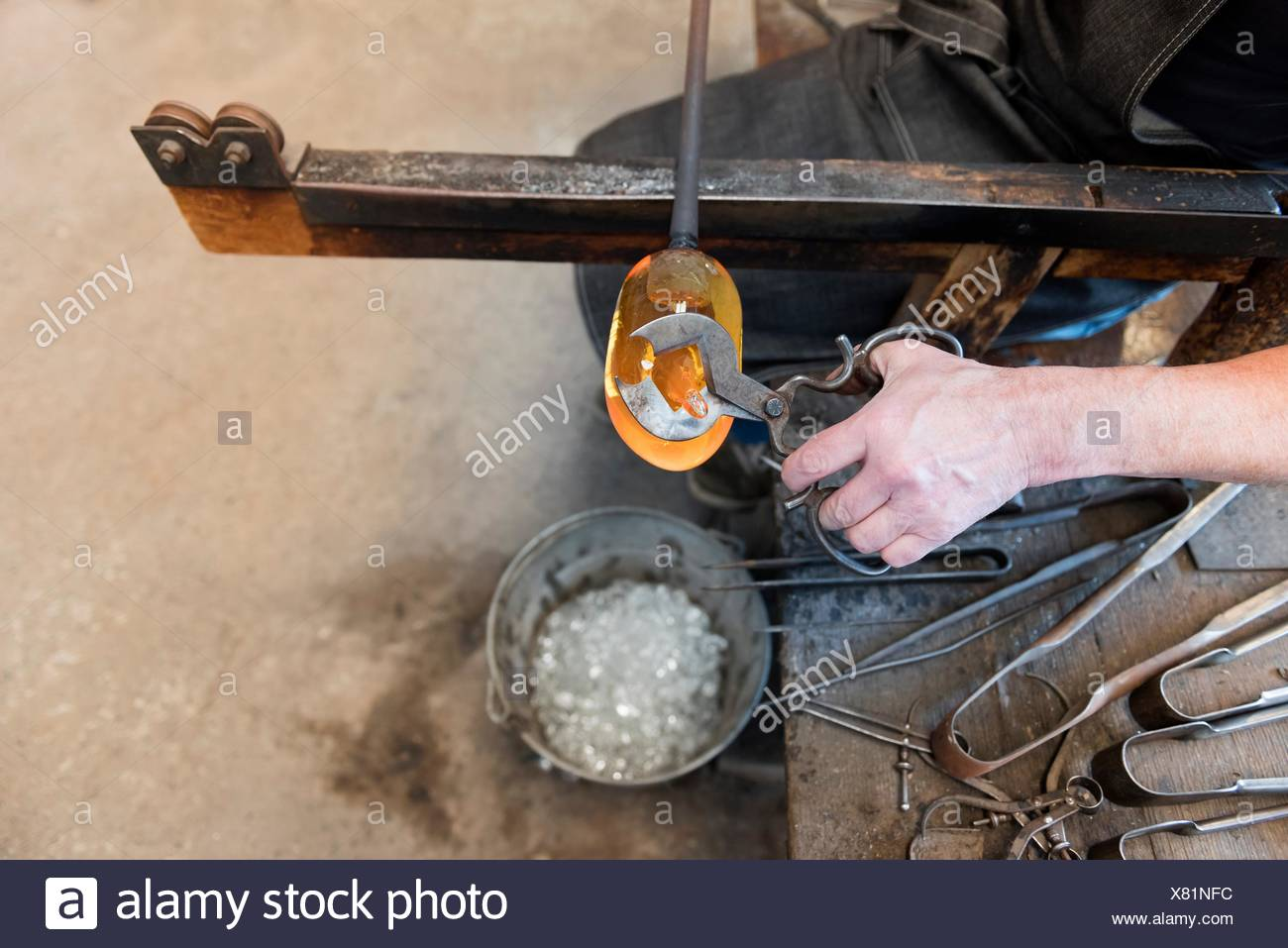 Glassblower using tool to trim molten glass in workshop, close up - Stock Image