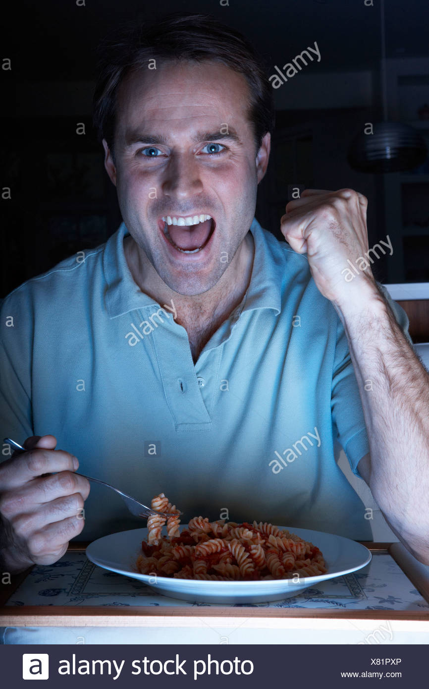 Man Enjoying Meal And Cheering Whilst Watching TV - Stock Image