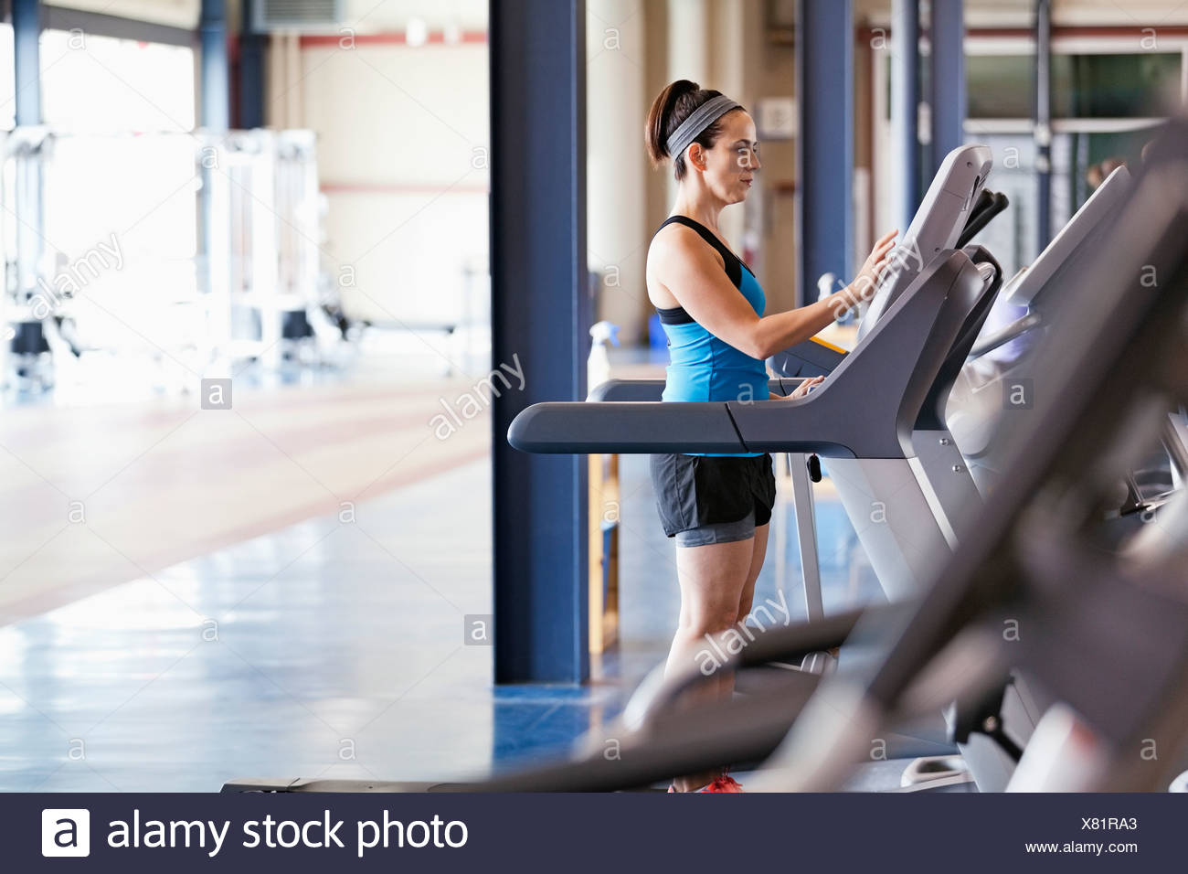 Woman exercising on treadmill in fitness center Stock Photo