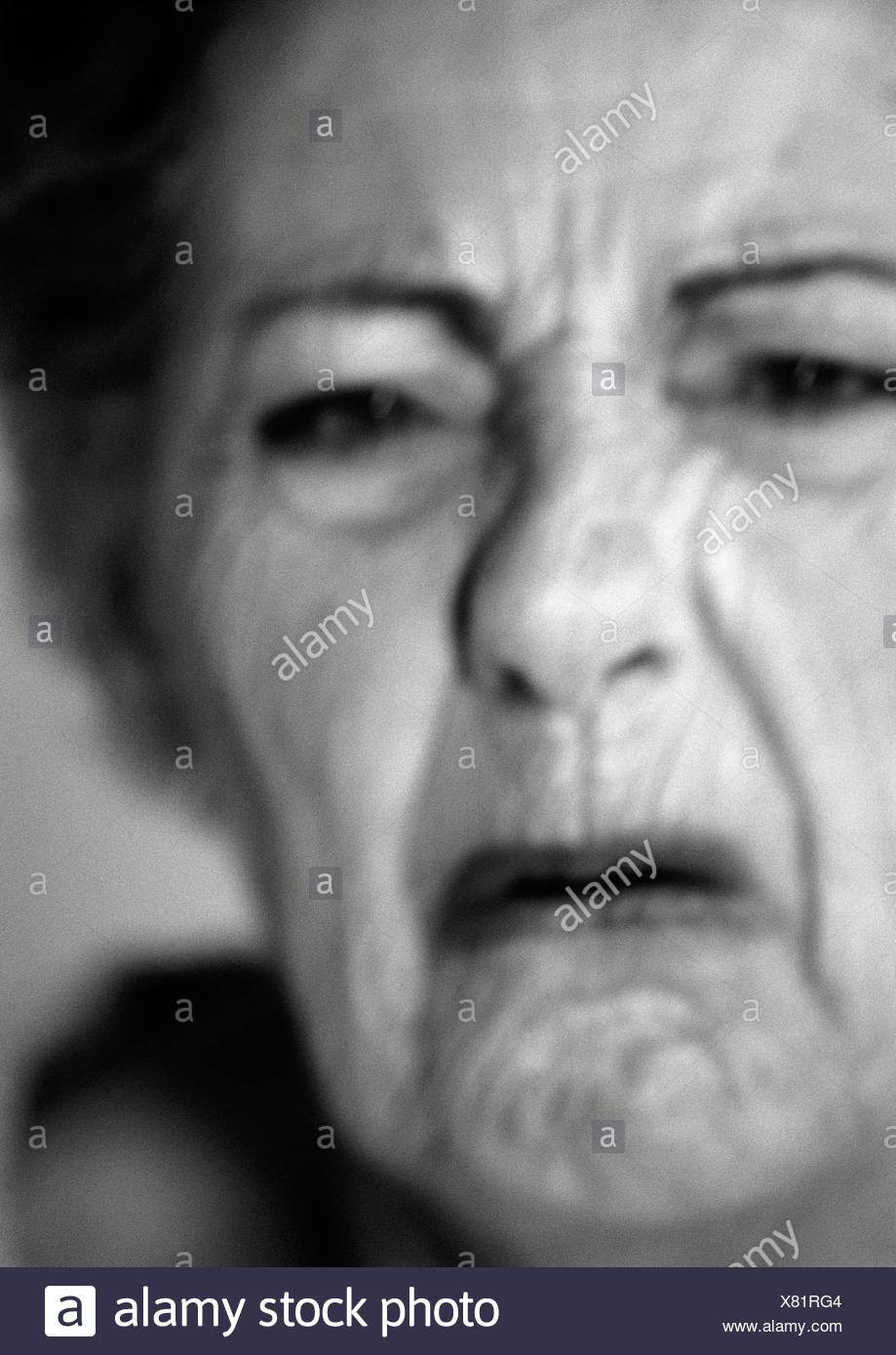 Senior woman frowning, close-up, portrait, b&w - Stock Image