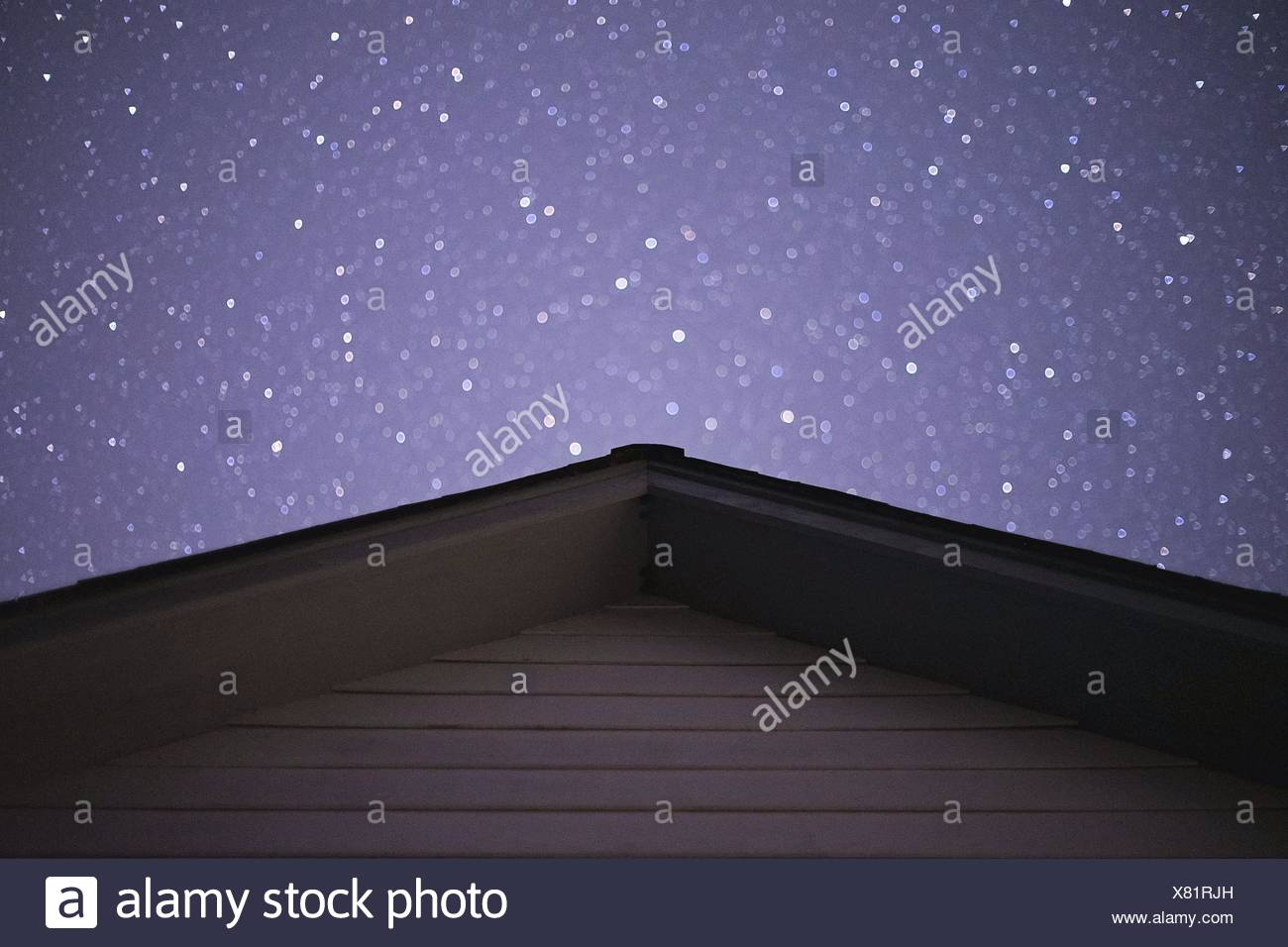 Stars above house's rooftop - Stock Image