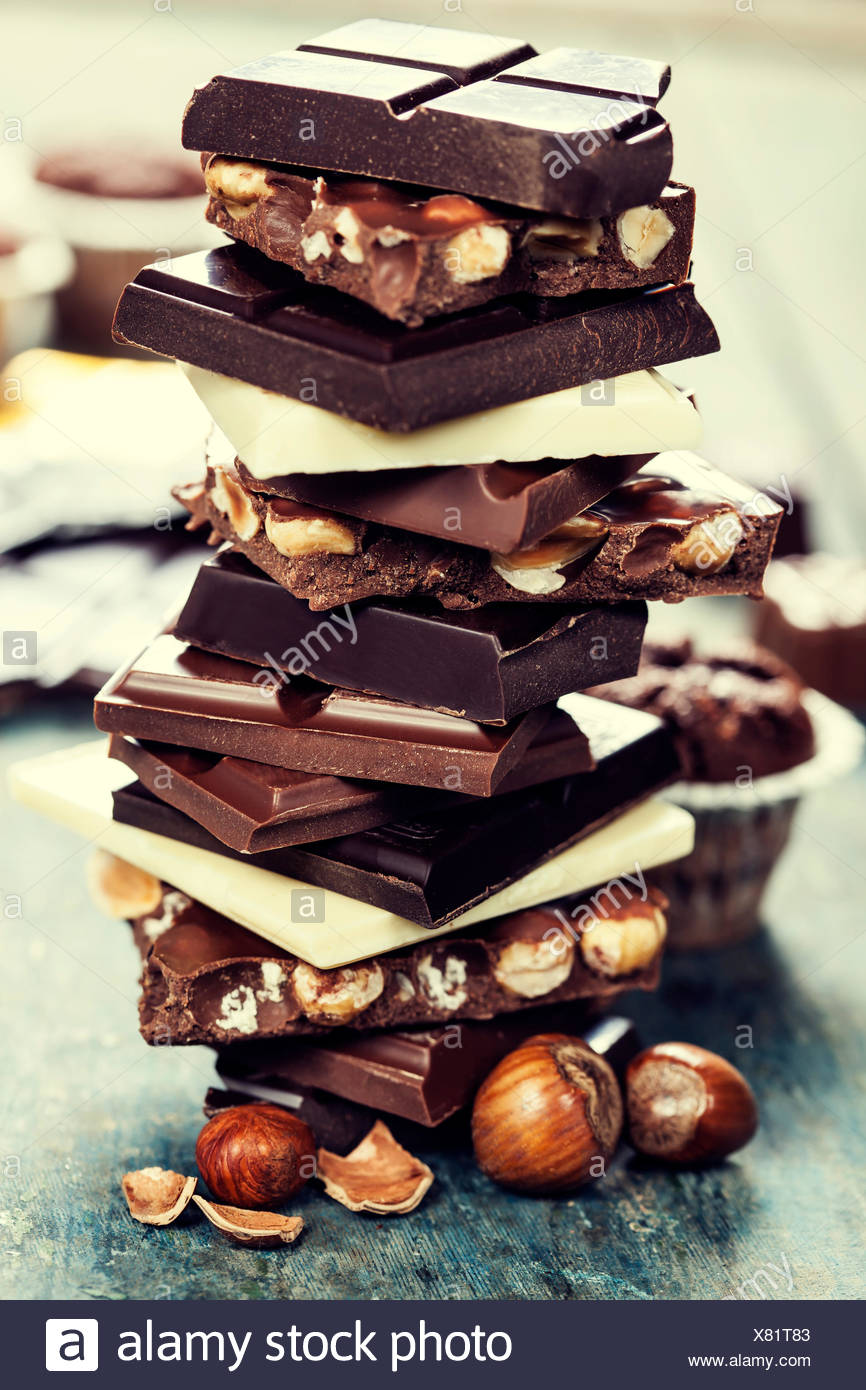 An assortment of  white, dark, and milk chocolate with nuts - on wooden board - Stock Image
