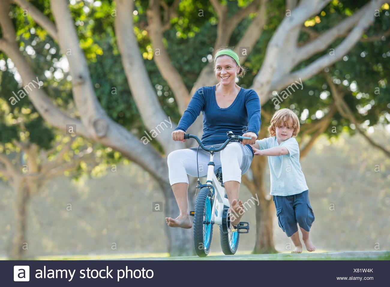 Mother sitting on son's bike, son pushing her along Stock Photo