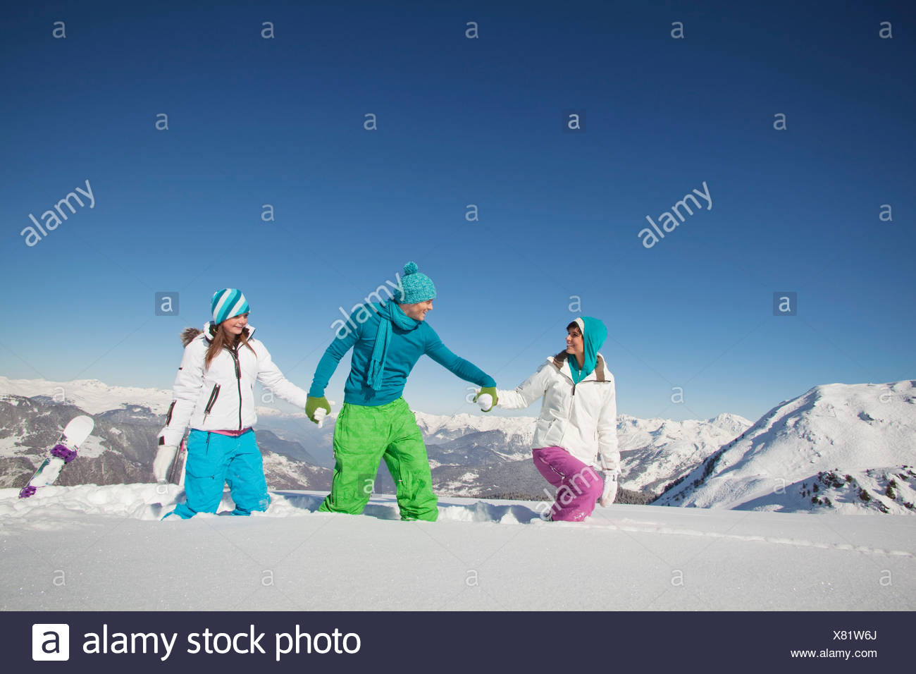 Couple and daughter walking in snow - Stock Image