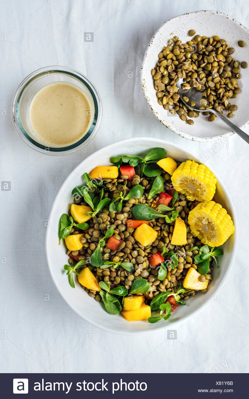 Lentil salad with herbs, tomatoes and peaches in a white bowl is photographed from top view. It is accompanied by cooked lentils in a bowl and tahini  - Stock Image