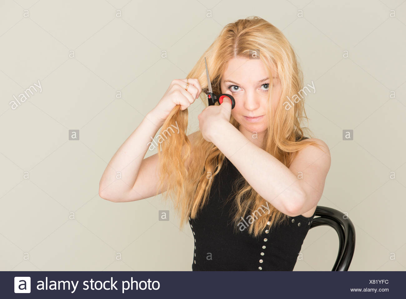 Teenage girl cutting her hair with scissors