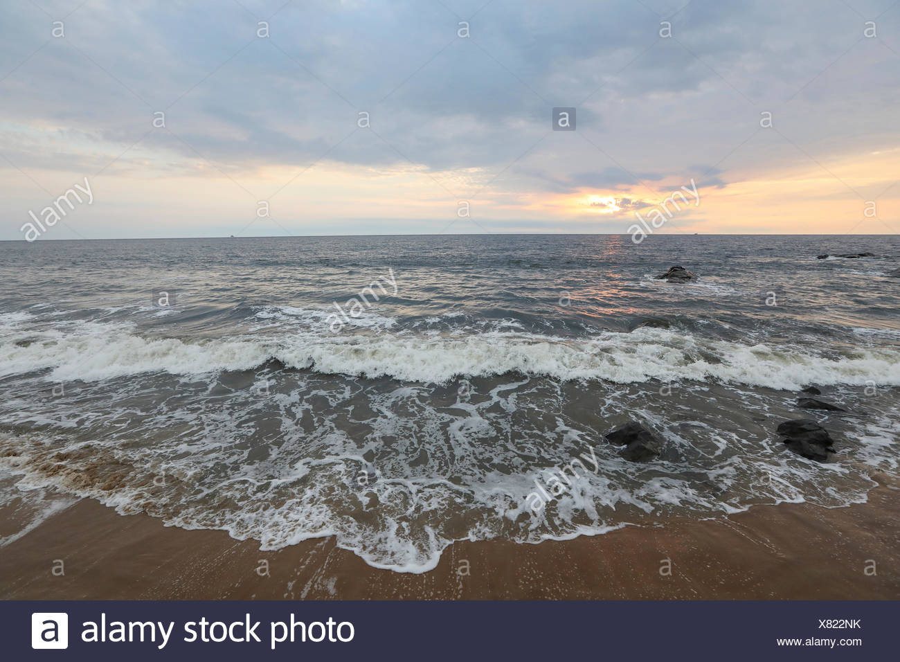 Waves wash up on the beach. - Stock Image
