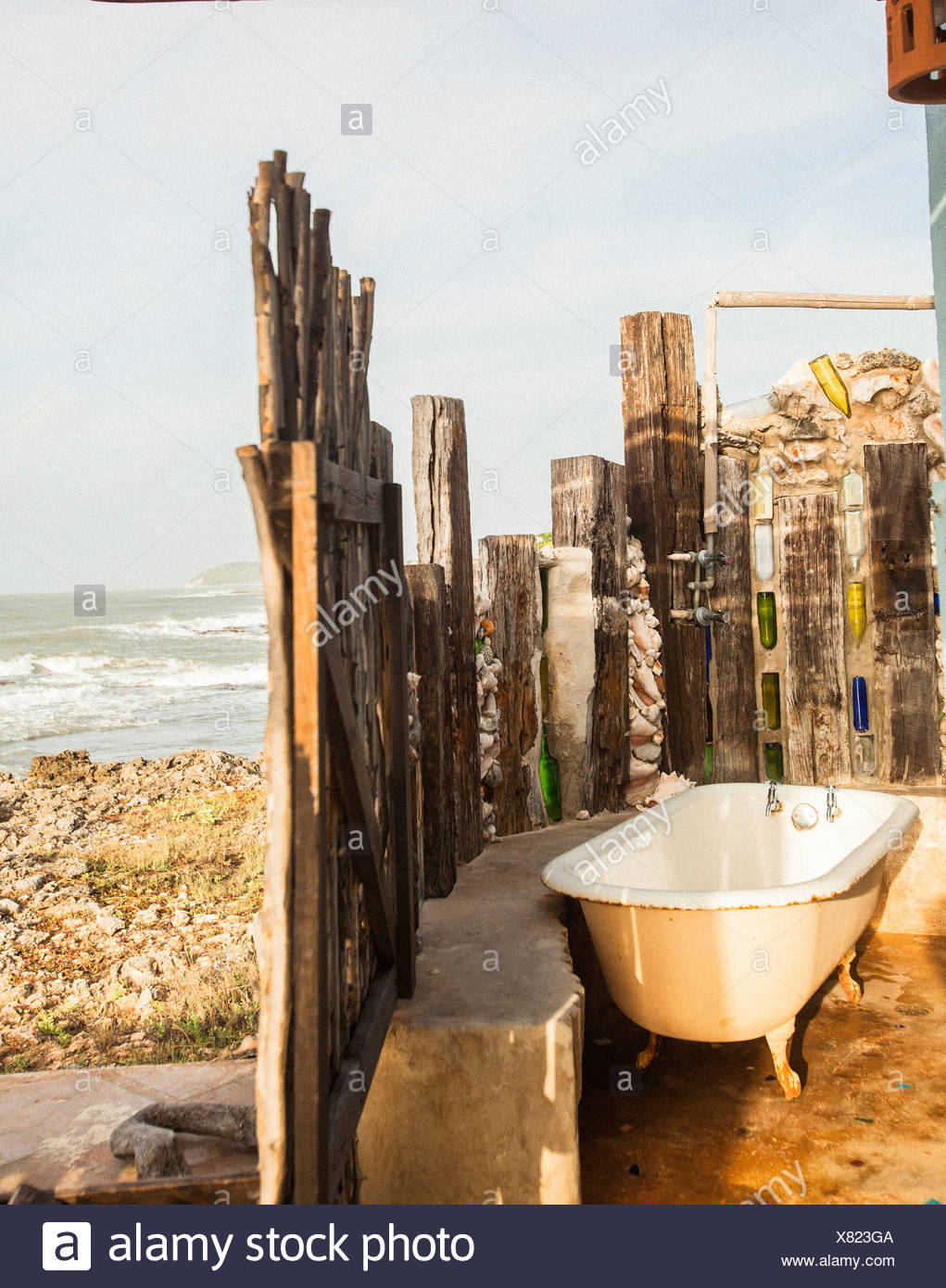 A bath tub and a wooden fence near the ocean shore. - Stock Image