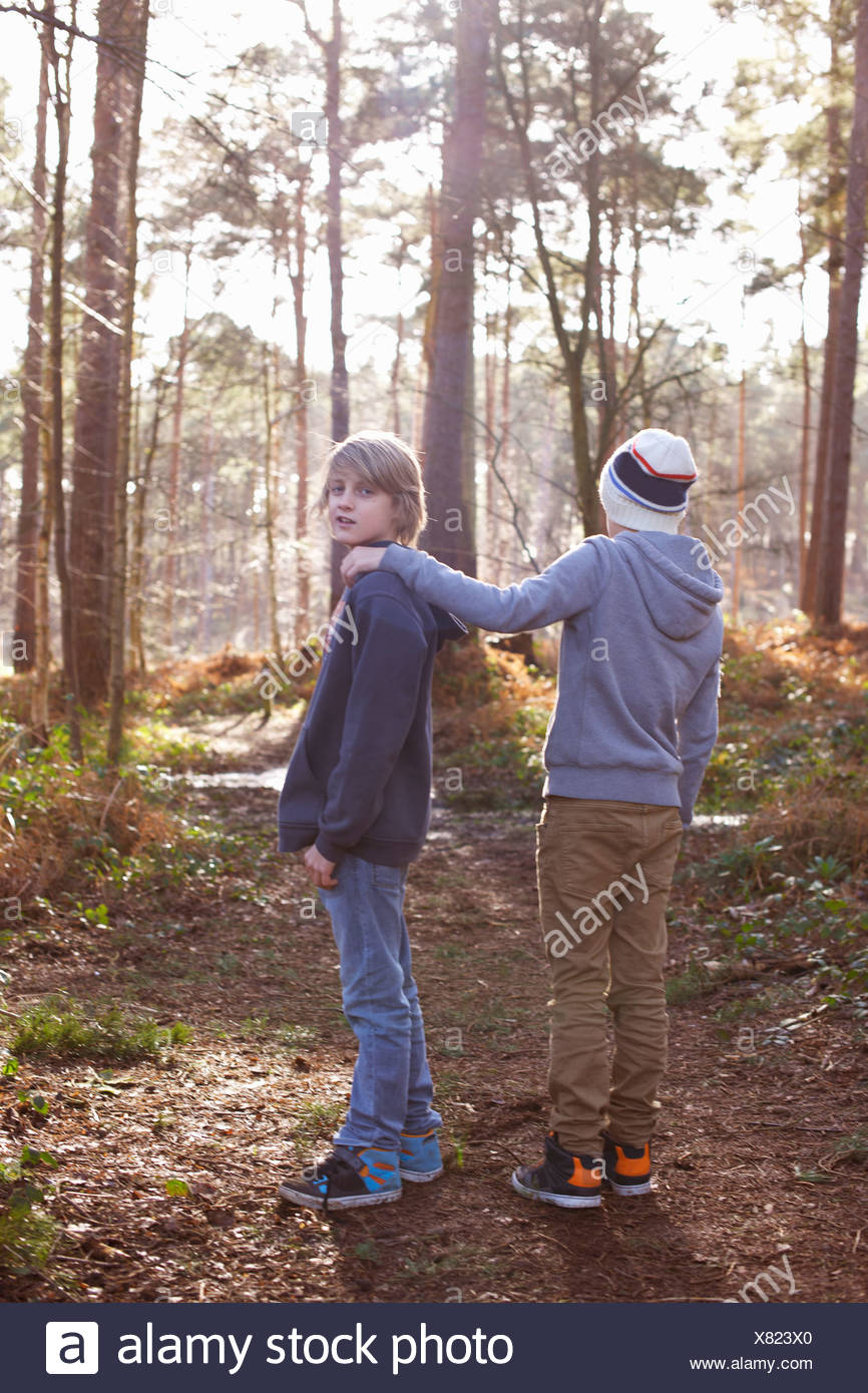 Twin brothers standing together in woods - Stock Image