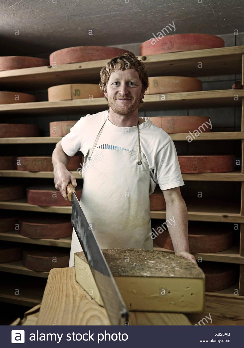Dairyman cutting a mountain cheese, Steinbergalm, Inneralpbach, Alpbach, Tyrol, Austria - Stock Image
