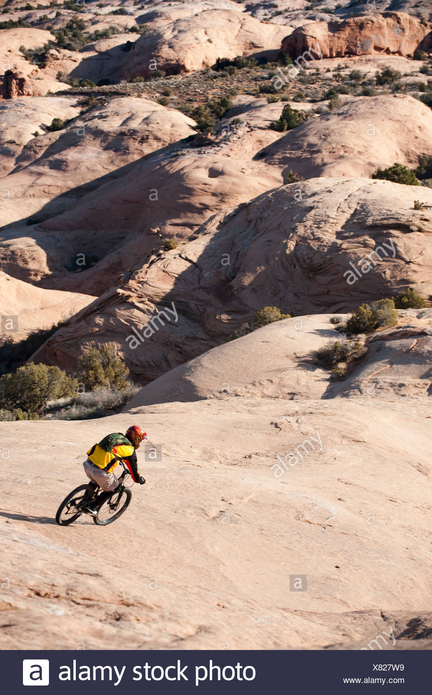 A young man rides his mountain bike on the Slickrock Trail, Moab, UT. - Stock Image