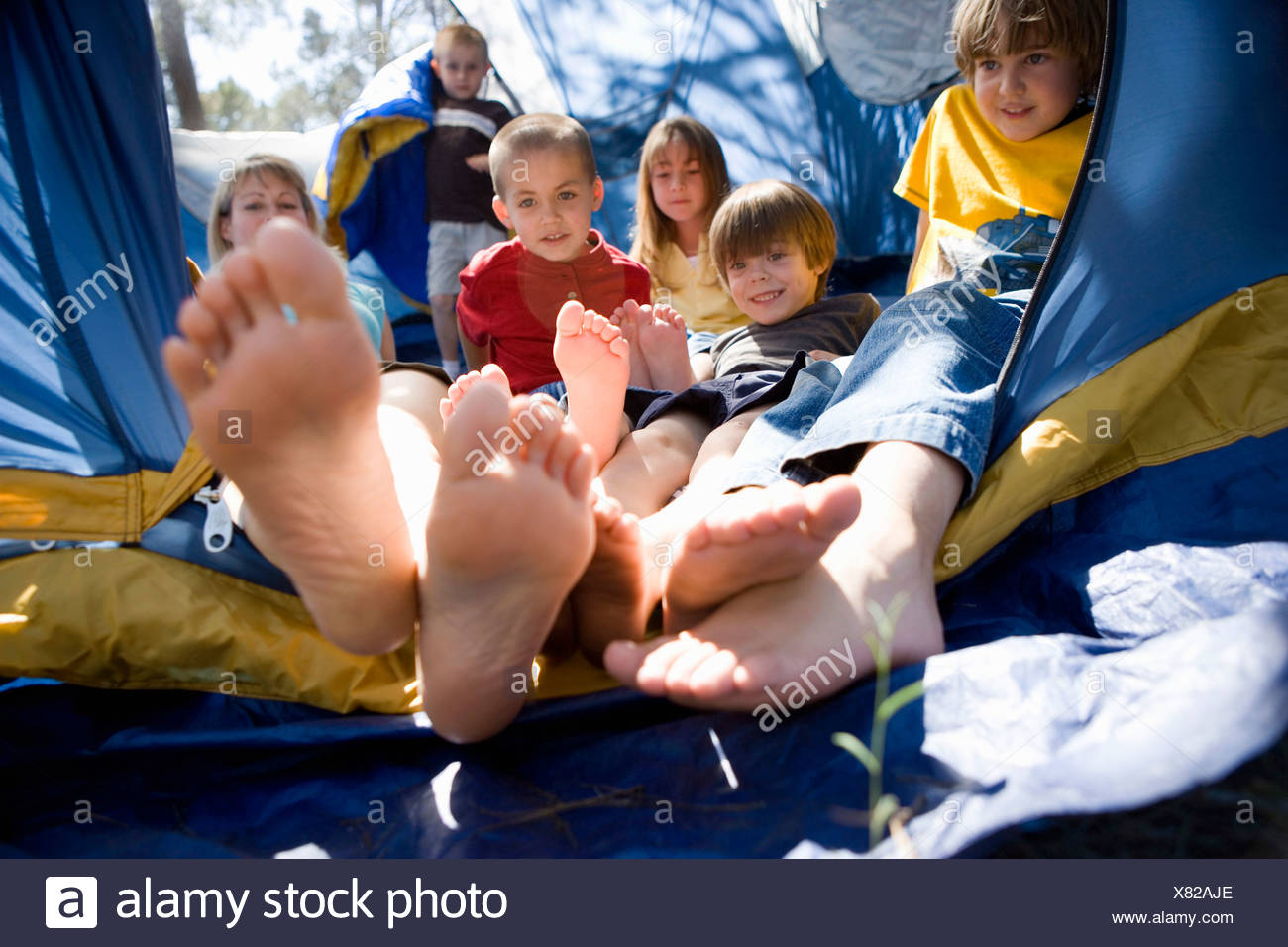 A woman and a group of children piled up in a tent - Stock Image