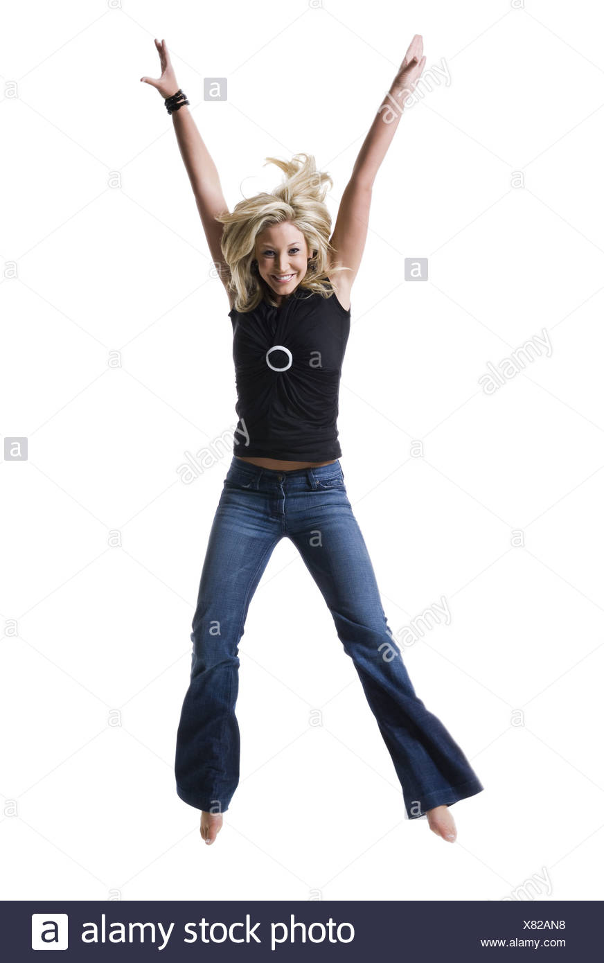 Portrait of a young woman jumping with her arms raised - Stock Image
