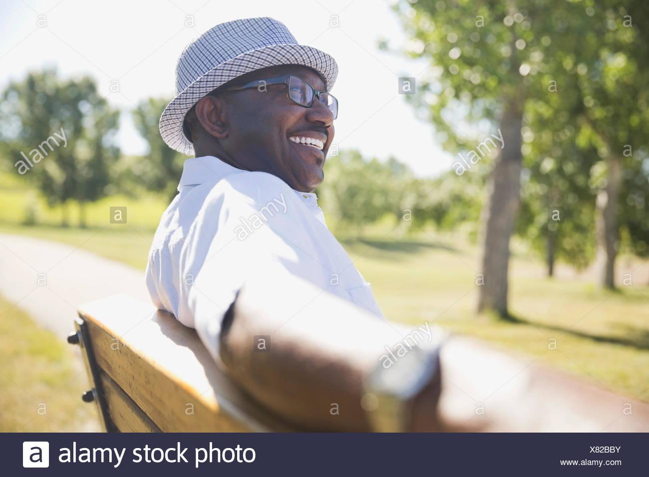 Smiling senior man sitting on park bench - Stock Image