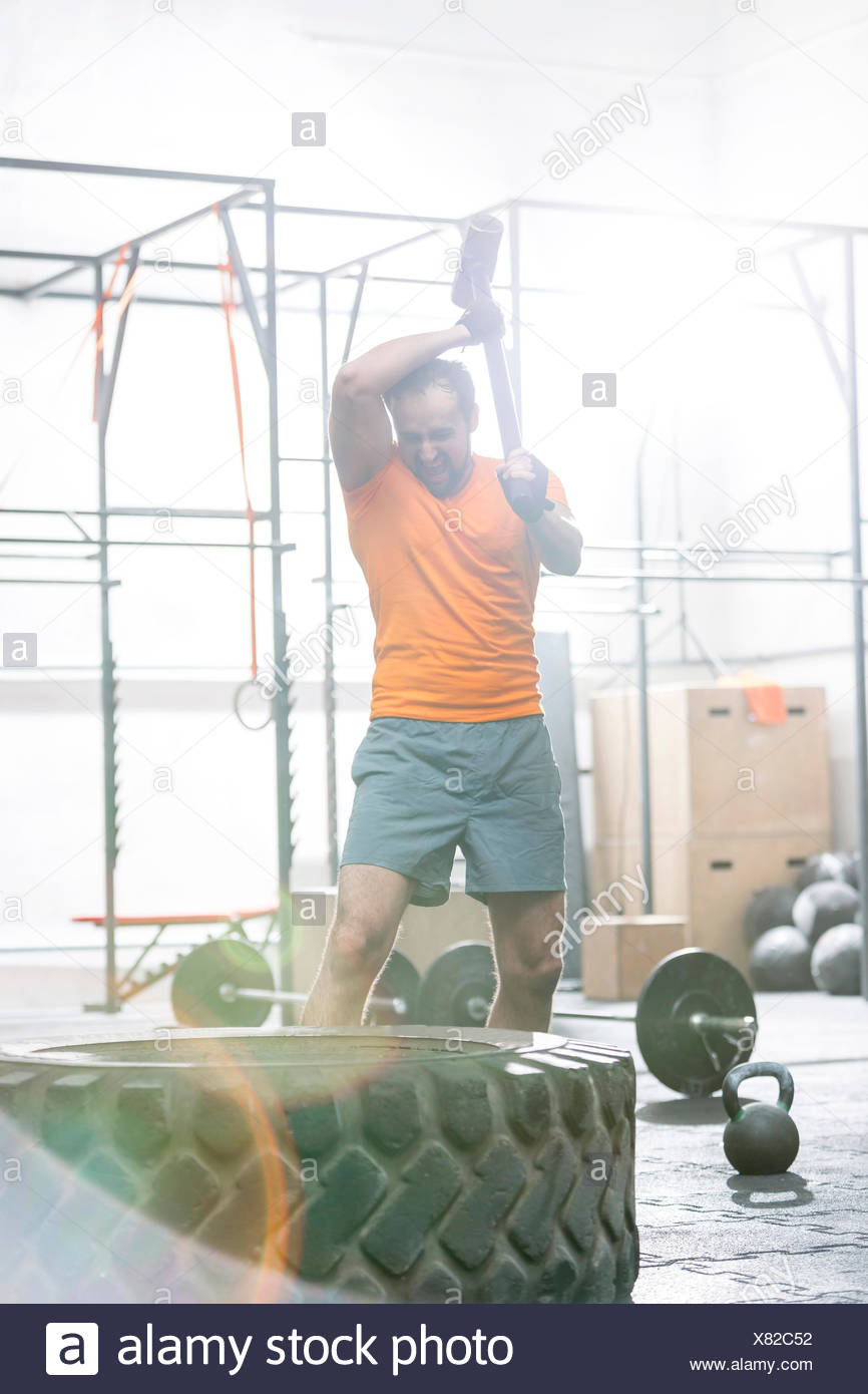 Determined man hitting tire with sledgehammer in crossfit gym - Stock Image