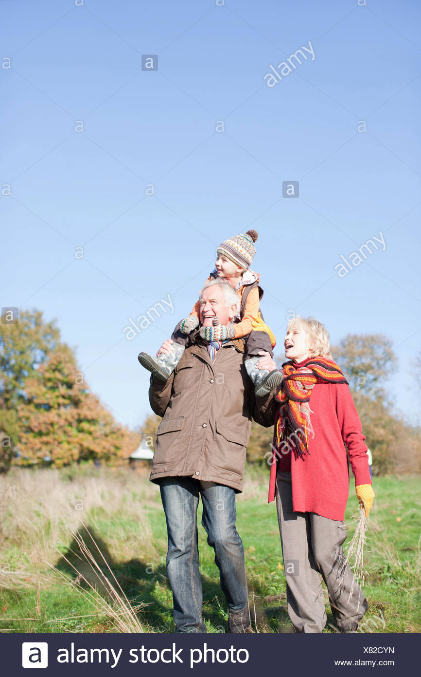 Grandparents walking outdoors with grandson - Stock Image