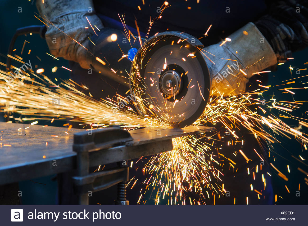 Cutting a steel plate with an angle grinder - Stock Image