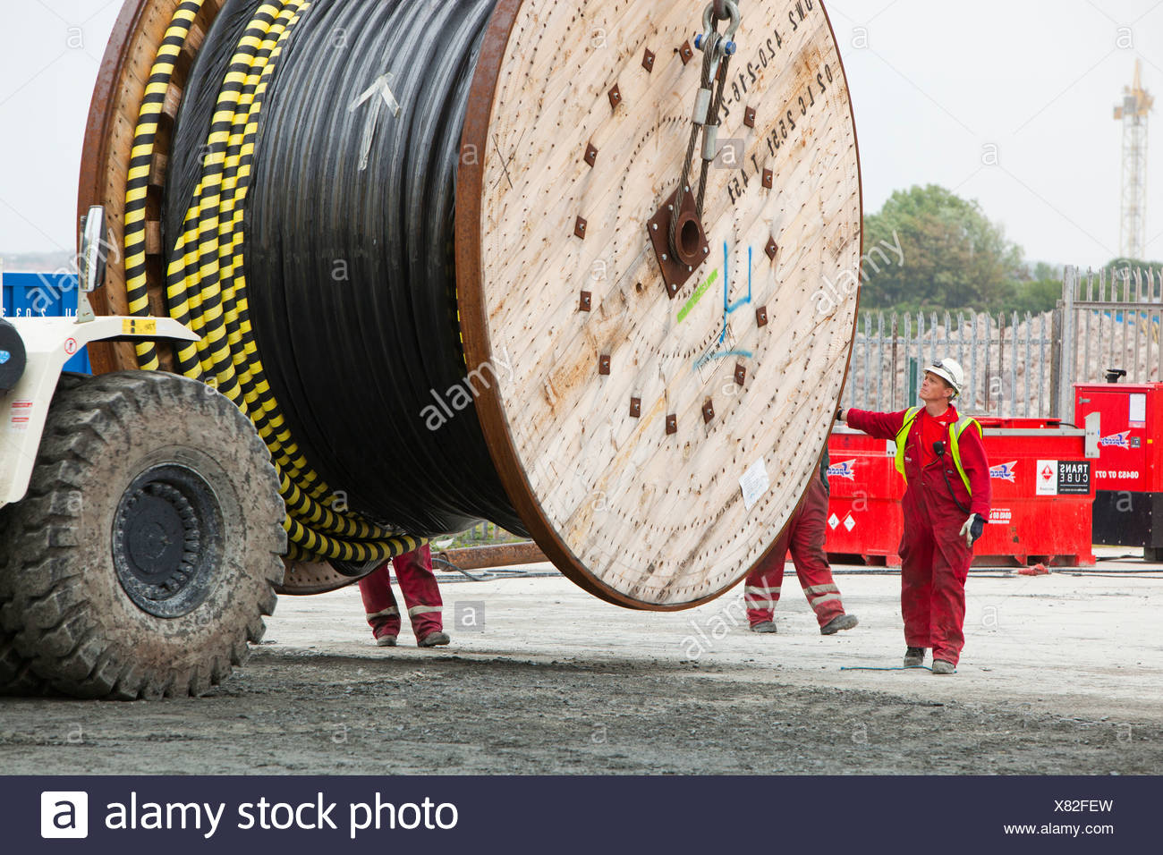 Offshore electric cabling for the Walney Offshore windfarm project being loaded onto a cable laying vessel in the docks - Stock Image
