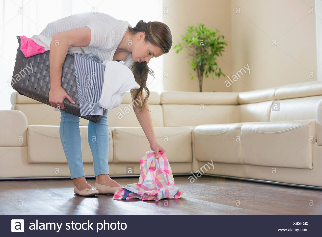 Woman with laundry basket picking clothes from floor in living room - Stock Image