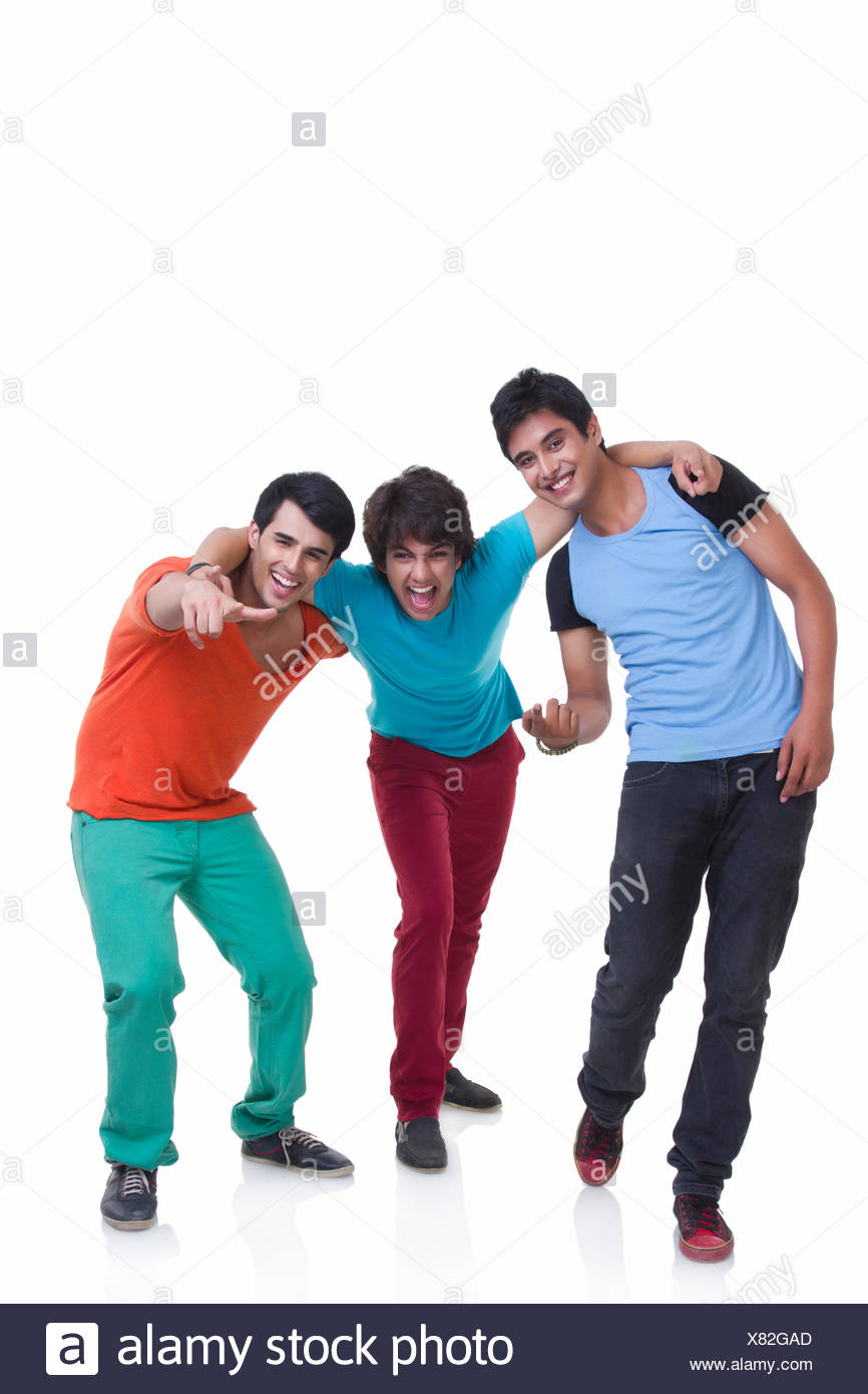 Full length of playful young male friends with arm around over white background - Stock Image