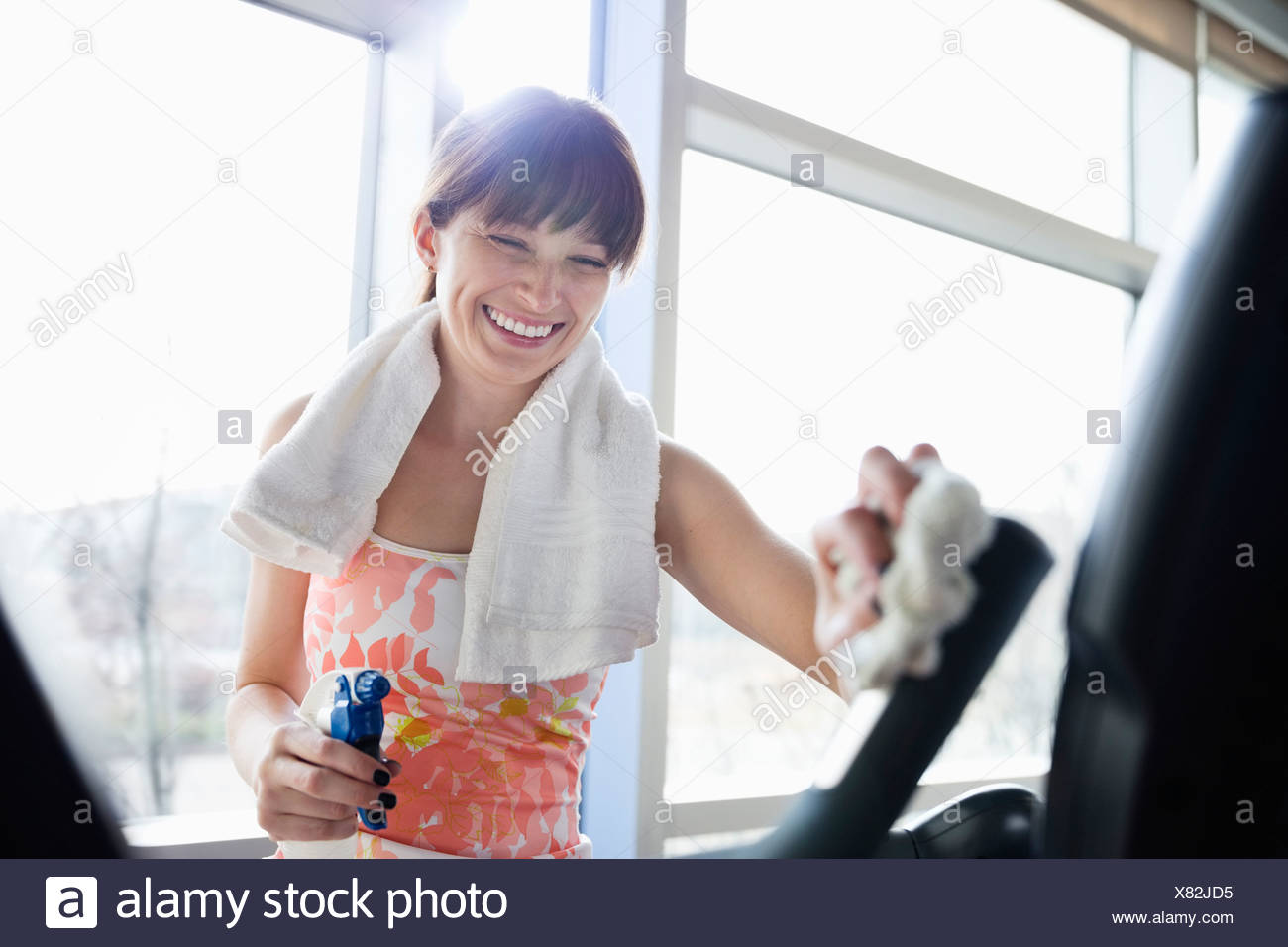 Woman cleaning stationary bike in fitness center - Stock Image