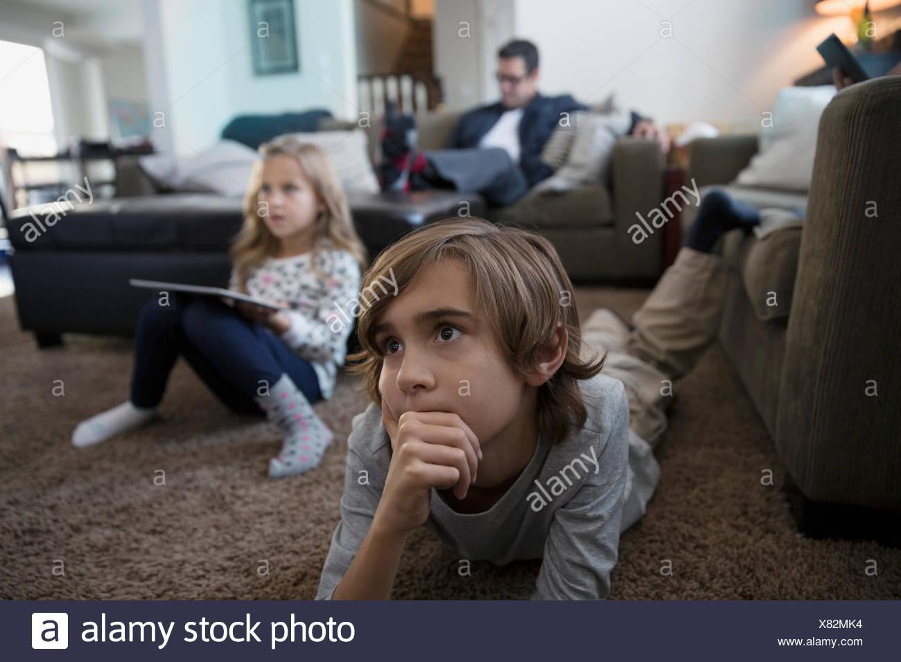 Serious boy watching TV on living room floor - Stock Image
