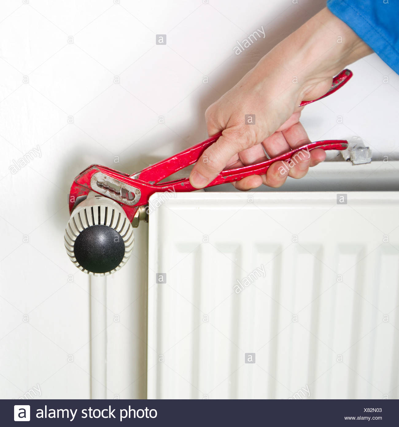 Plumber and radiator - Stock Image