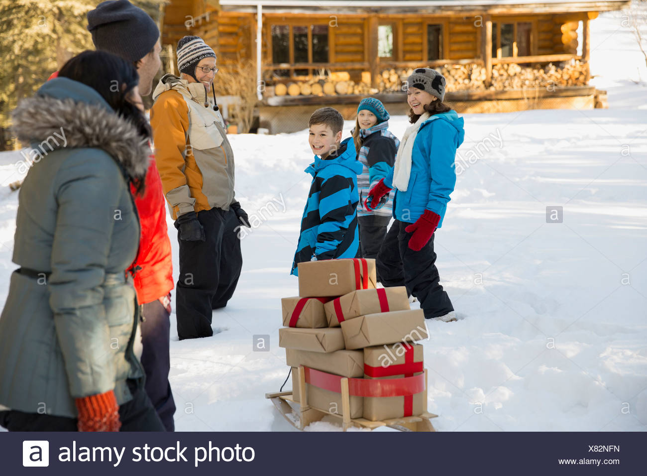 Family walking to cabin with stack of gifts Stock Photo