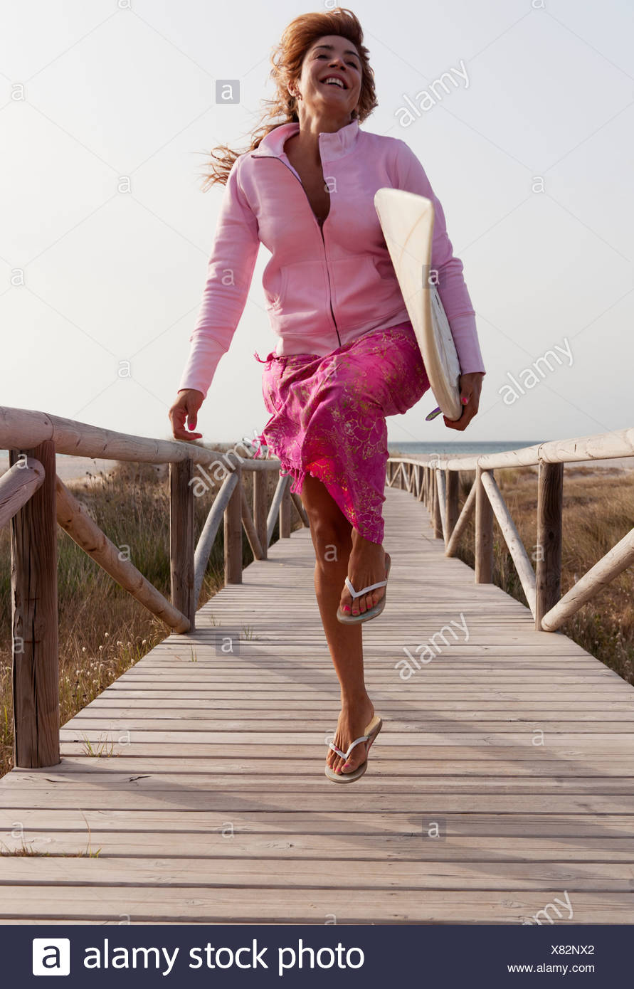 A Young Woman Skipping Down A Wooden Boardwalk With A Surfboard; Tarifa, Cadiz, Andalusia, Spain - Stock Image