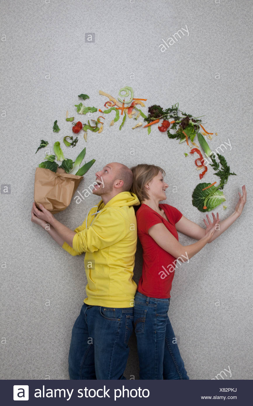 Man and woman balancing vegetables - Stock Image