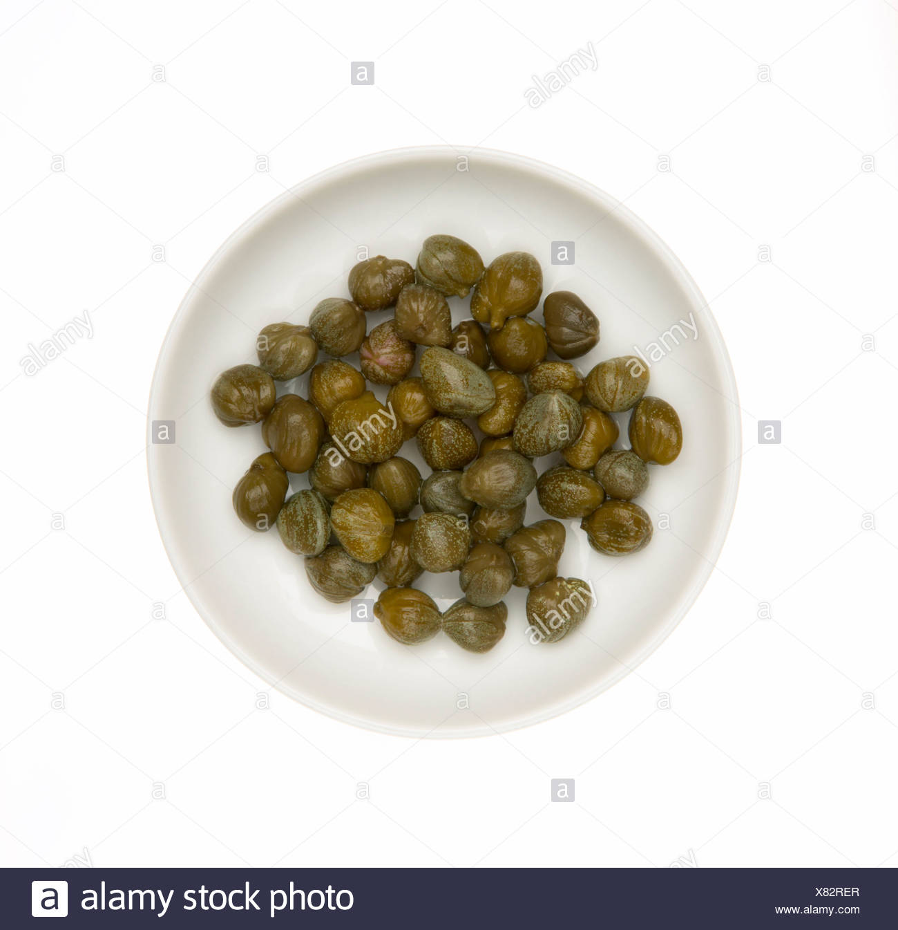 Capers on dish, elevated view - Stock Image