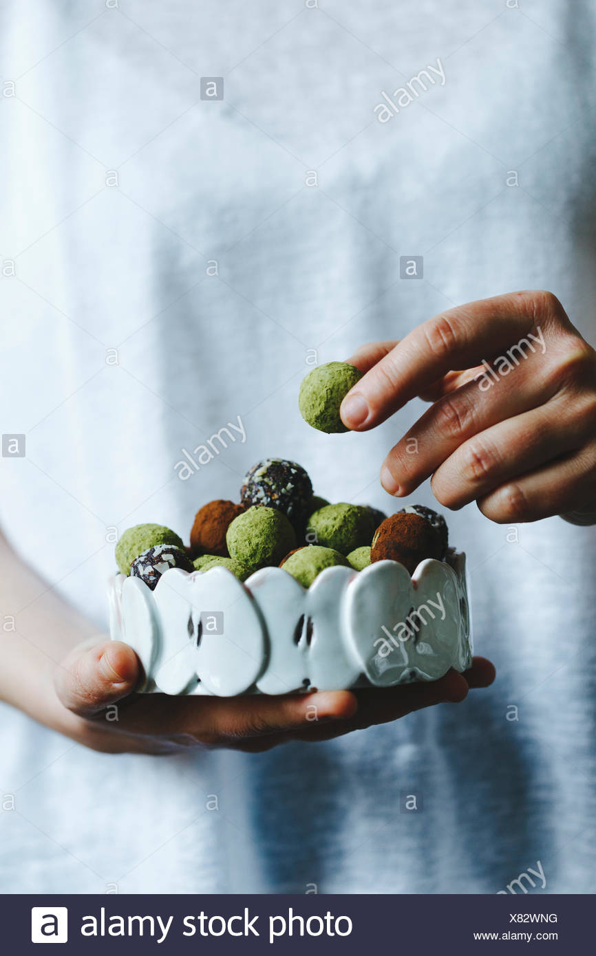 A woman holding a bowl of mixed matcha and chocolate homemade sweets Stock Photo