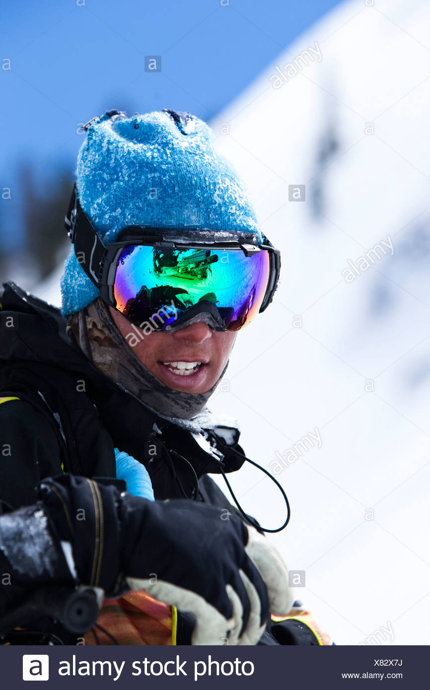 A portrait of a snowboarder smiling with a reflection of a snowmobile in his goggles in the backcountry of Colorado. - Stock Image