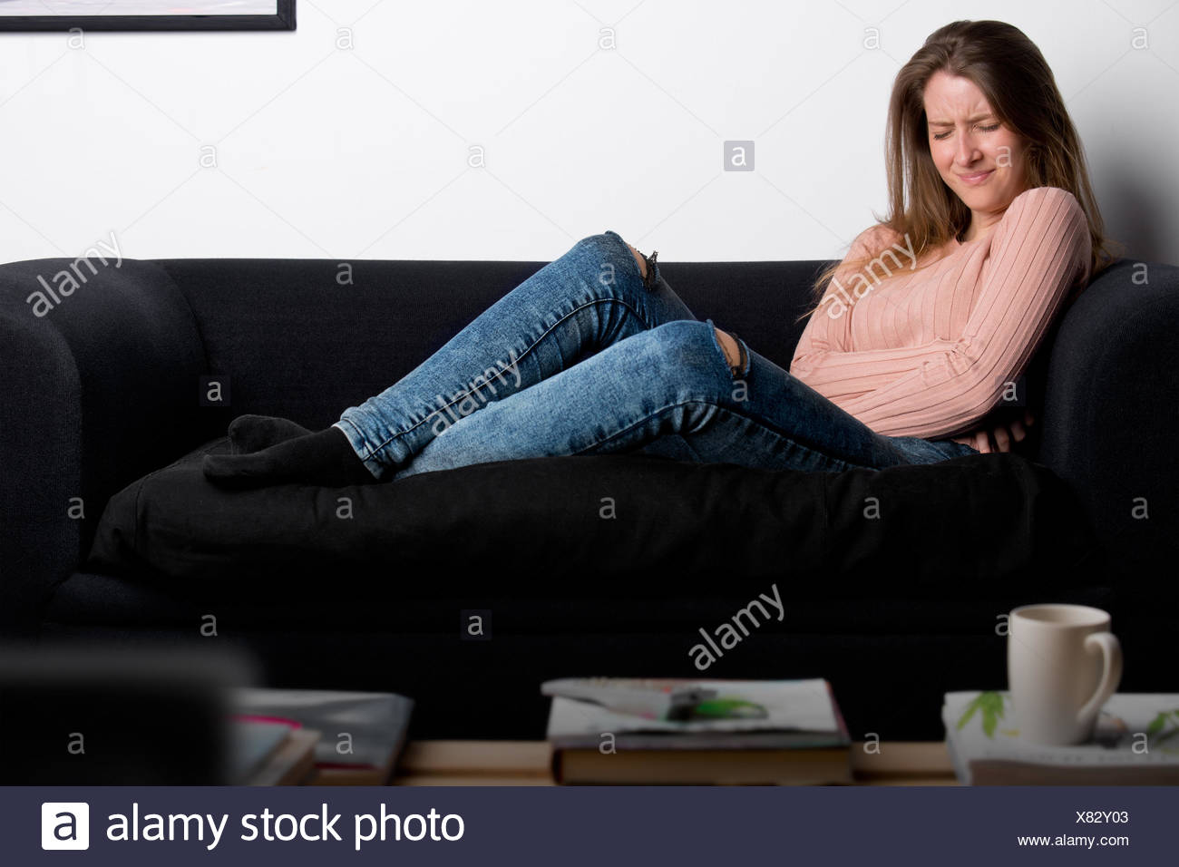 Woman in Pain on a Couch - Stock Image