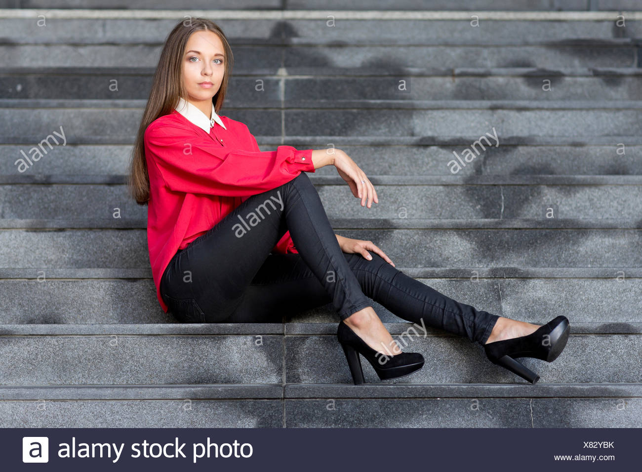 f4764c9ed57c10 Young woman wearing a red top, black jeans and high heels posing while  sitting on stairs