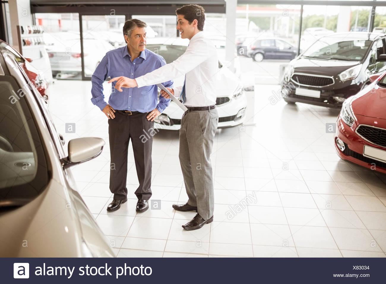 Salesman showing somethings to a man - Stock Image