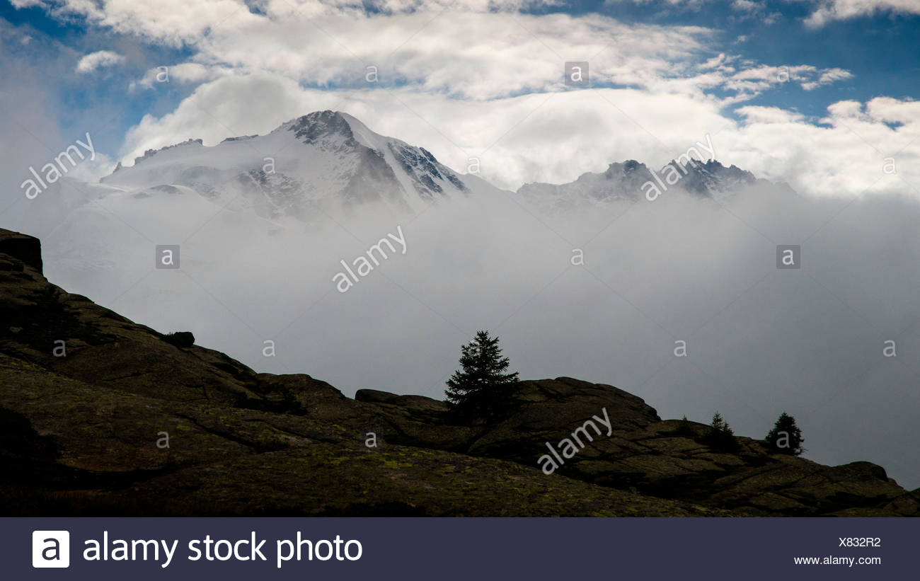 Morning's light behind low clouds, with Gran Paradiso and Piccolo Paradiso in the background. (Valsavarenche, Aosta Valley, Italy) - Stock Image