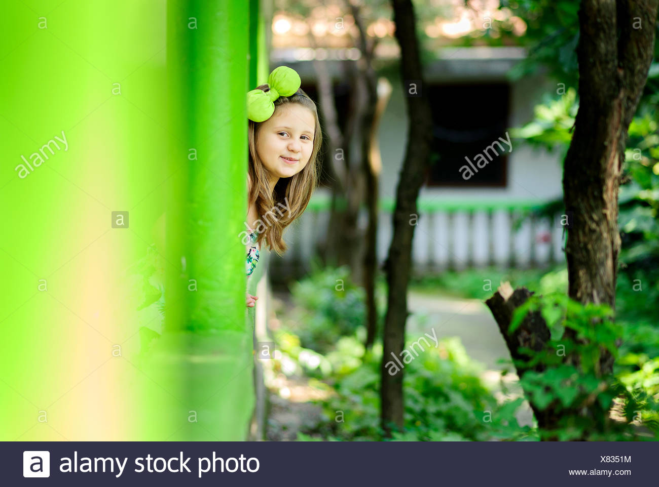 Girl (6-7) playing hide-and-seek - Stock Image