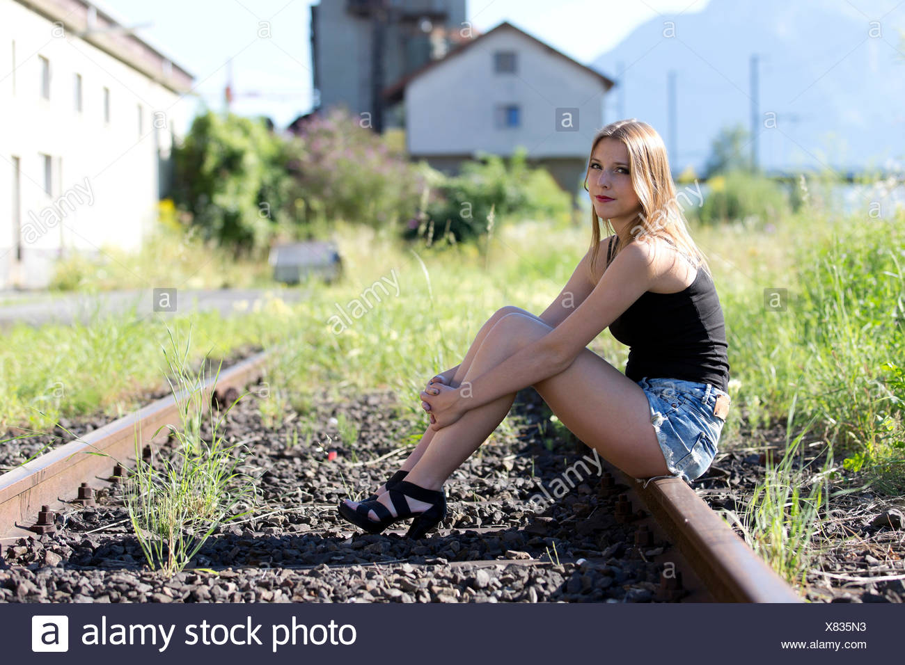 Young woman in a black top, jeans hot pants and high heels posing sitting on railway tracks - Stock Image