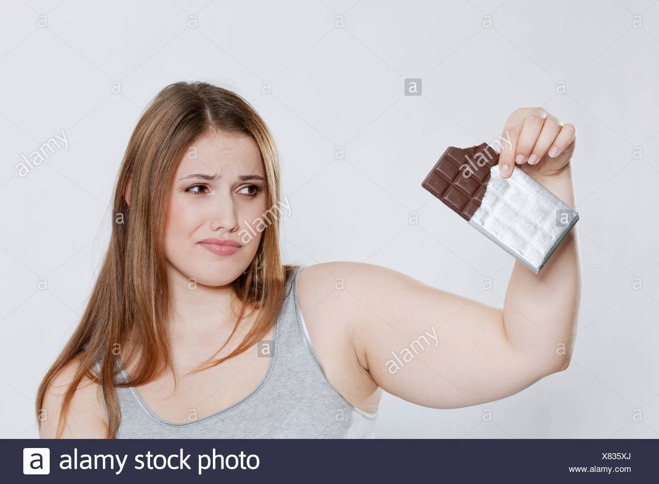 Young chubby woman with chocolate bar - Stock Image