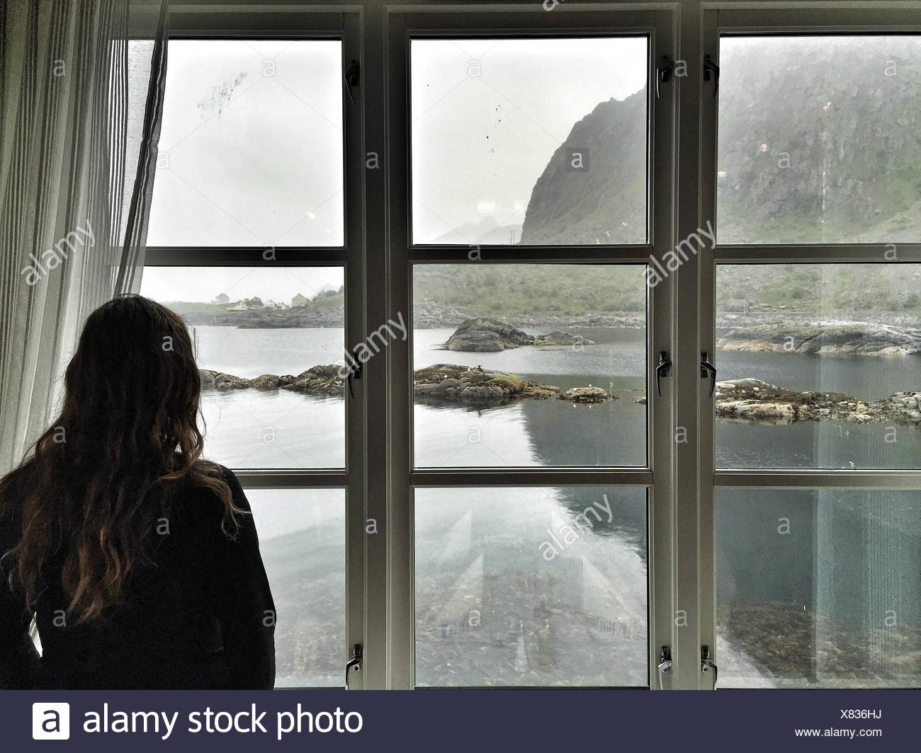 Rear View Of Woman Looking River And Mountain Through Window - Stock Image