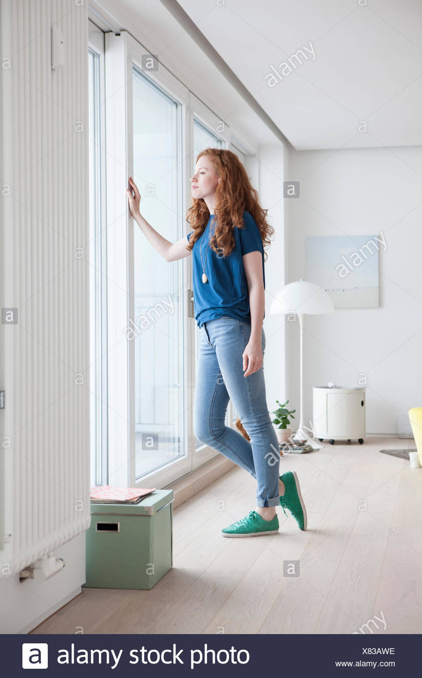 Young woman standing in her living room looking through window - Stock Image