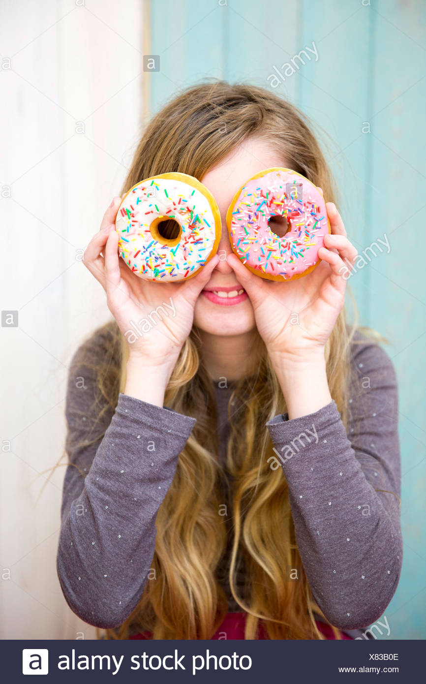 Girl looking through donuts - Stock Image