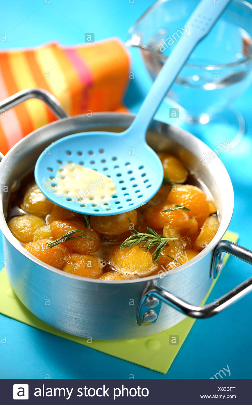 Cooking the apricots with sugar and rosemary - Stock Image